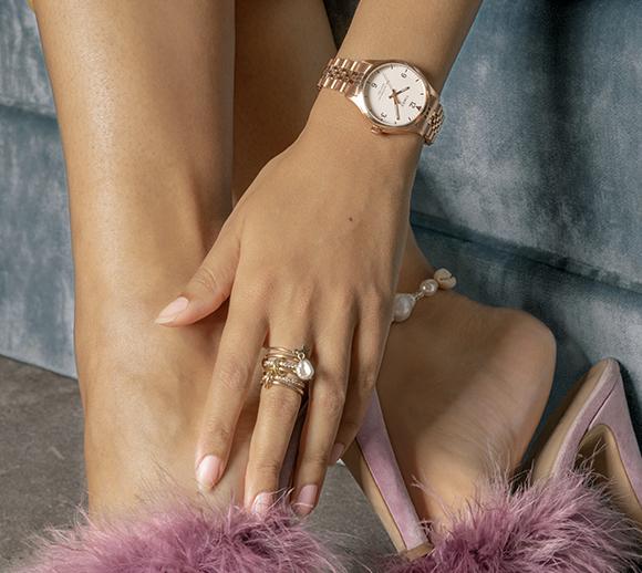 partie inférieure du corps d'une femme portant une montre Waterbury rose doré et d'autres bijoux